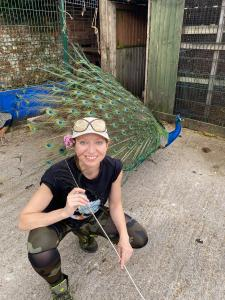 Caroline-with-Duran-the-peacock-about-to-display